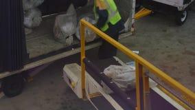 Arbetaren laddar påsar av post på kommersiellt flyg på flygplatsen arkivfilmer