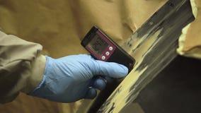 Arbetaren mäter en tjocklek av abc-bok på en kropp för bil` som s använder ett tjockleksmått 4K arkivfilmer