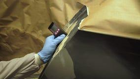 Arbetaren mäter en tjocklek av abc-bok på en kropp för bil` som s använder ett tjockleksmått 4K lager videofilmer
