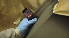 Arbetaren mäter en tjocklek av abc-bok på en kropp för bil` som s använder ett tjockleksmått 4K stock video