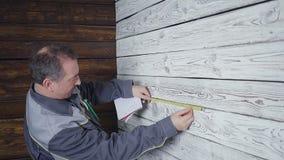 Arbetaren mäter en trävägg med en linjal lager videofilmer