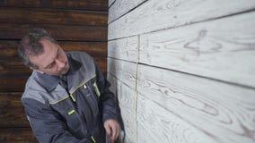 Arbetaren mäter en trävägg med en linjal arkivfilmer