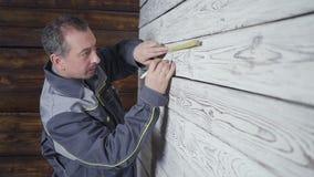 Arbetaren mäter en trävägg med en linjal stock video