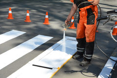Arbetaren målar en fot- övergångsställe Den tekniska målning för vägmanarbetaren och anmärkaövergångsstället fodrar på asfalt s Royaltyfria Foton