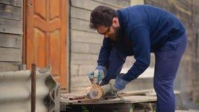 Arbetaren med ett skägg och i gul skyddsglasögon sågar röret med en slipande maskin stock video