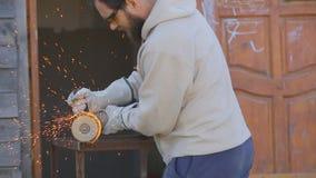Arbetaren med ett sk?gg s?tter p? handskar och s?gar r?ret med en slipande maskin stock video