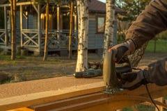 Arbetaren med hjälp av hjälpmedlet utför arbete med wood fiberplattaisolering Royaltyfri Bild
