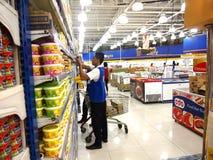 Arbetaren ordnar livsmedelsprodukter på en hylla i en livsmedelsbutik Royaltyfri Fotografi