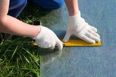 arbetaren på enheten av växthusen, sade handtaget, för bitande polycarbonate, utomhus royaltyfria foton