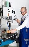 Arbetaren på malning bearbetar med maskin Royaltyfri Fotografi