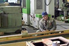 Arbetaren polerar abc-boklagret Arkivbilder