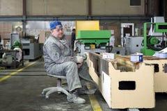 Arbetaren polerar abc-boklagret Arbete på förberedelsen av maskinsängen för följande målning Royaltyfri Foto