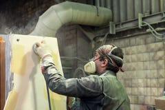 Arbetaren polerar abc-boklagret Arbete på förberedelsen av maskinsängen för följande målning Royaltyfri Bild