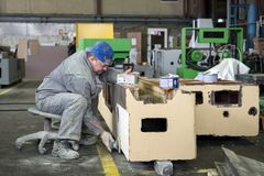 Arbetaren polerar abc-boklagret Arbete på förberedelsen av maskinsängen för följande målning Arkivfoton