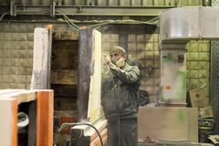 Arbetaren polerar abc-boklagret Arbete på förberedelsen av maskinsängen för följande målning Royaltyfria Foton