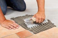 Arbetaren räcker fördelande bindemedel för keramiska golvtegelplattor arkivbild