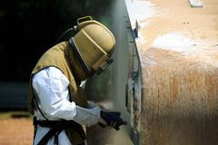 Arbetaren är tar bort målarfärg, genom att spränga för sand för lufttryck Fotografering för Bildbyråer