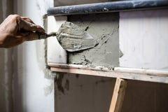 Arbetaren rappar cement på väggen arkivfoton