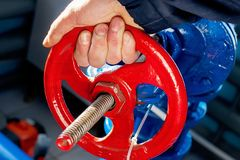 Arbetaren rotera den röda ventilen och stängde av gastillförselen Hand- och ventilcirkelnärbild royaltyfria foton