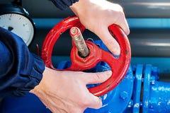 Arbetaren rotera den röda ventilen och stängde av gastillförselen Hand- och ventilcirkelnärbild royaltyfri fotografi