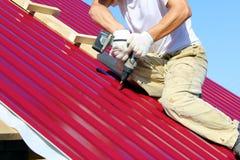 Arbetaren roterar skruven på taket royaltyfria foton