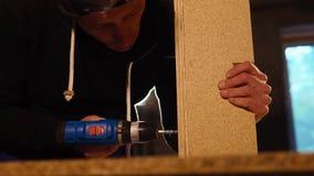 Arbetaren rymmer ett elektriskt borrar in hans händer för att vrida spikar in i brädet arkivfilmer