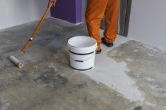 Arbetaren sätter abc-bok med rullen på konkret golv Arkivbilder