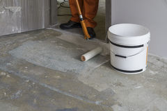 Arbetaren sätter abc-bok med rullen på konkret golv Royaltyfri Fotografi
