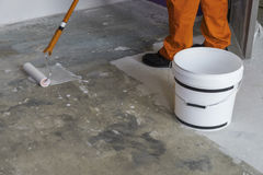 Arbetaren sätter abc-bok med rullen på konkret golv Hus under Co Royaltyfri Fotografi