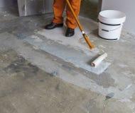 Arbetaren sätter abc-bok med rullen på konkret golv i rum av unfien Arkivfoton