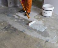 Arbetaren sätter abc-bok med rullen på konkret golv i rum från FN Royaltyfria Bilder