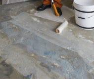 Arbetaren sätter abc-bok med rullen på konkret golv Rum av huset Fotografering för Bildbyråer