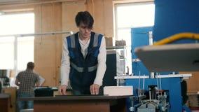 Arbetaren sätter in ark av papper till printingmaskinen, polygrafbransch lager videofilmer