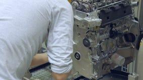 Arbetaren sätter bultar in i bilmotorn, modern bilproduktion, seminarium arkivfilmer