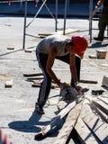 Arbetaren sågar med en cirkelsåg på gatan royaltyfri bild