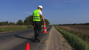 Arbetaren satte kottar på kanten av huvudvägen lager videofilmer