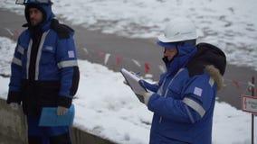 Arbetaren skriver på ett ark av papper lager videofilmer