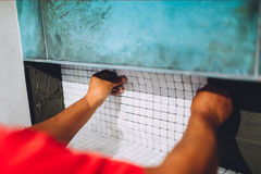 Arbetaren som förlägger den keramiska mosaiken, stiger ombord på böjligt bindemedel Arbetaren räcker arbete med keramiska tegelpl Arkivbild