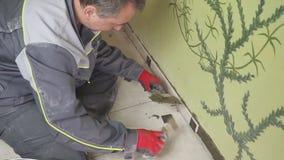 Arbetaren ställer in små tegelplattor på väggen i köket Hans händer förlägger tegelplattan på bindemedlet stedikamskytte lager videofilmer