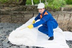 Arbetaren stänger stenarna med en vit torkduk för att skapa en konstgjord pöl arkivfoto