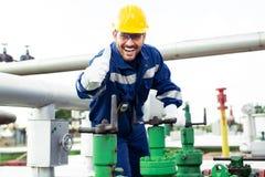 Arbetaren stänger ventilen på den olje- rörledningen royaltyfri fotografi