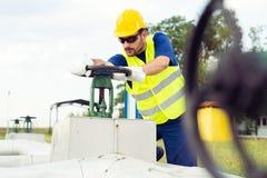 Arbetaren stänger ventilen på den olje- rörledningen royaltyfri bild