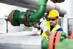 Arbetaren stänger ventilen på den olje- rörledningen royaltyfria bilder