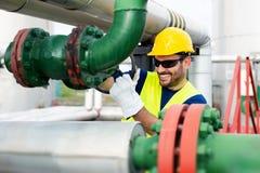 Arbetaren stänger ventilen på den olje- rörledningen arkivfoto