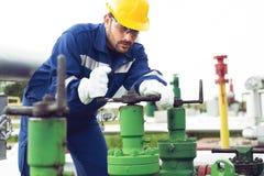 Arbetaren stänger ventilen på den olje- rörledningen royaltyfria foton