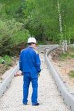 Arbetaren står och rymmer i hans händer nivån som mäter lutningen av vägen som byggs arkivbilder