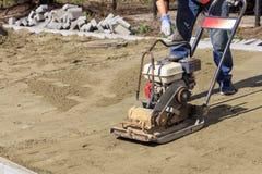 Arbetaren startar en bensincompactor för att ramma sandig jord för att lägga stenläggningtjock skiva royaltyfri bild