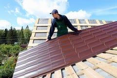 Arbetaren sätter metalltegelplattorna på taket Arkivbilder