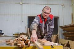 Arbetaren tar bort den färdiga delen, når han har klippt maskinen Arkivfoton