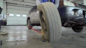 Arbetaren tar bort hjulet från bilen lager videofilmer